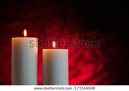 two candles lit with red background