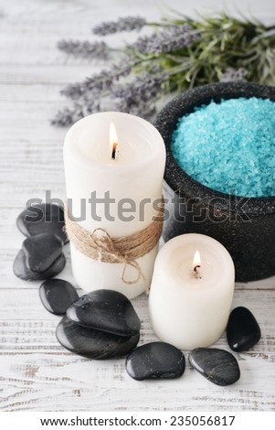 Two candles with lavender flowers and sea salt in bowl on light blue background