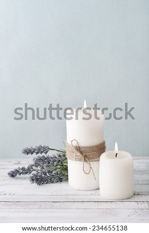 Two candles with lavender flowers on light blue background - stock photo