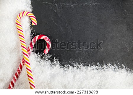 Two Candy Canes On Black Background With Snow Around. Copy Space - stock photo