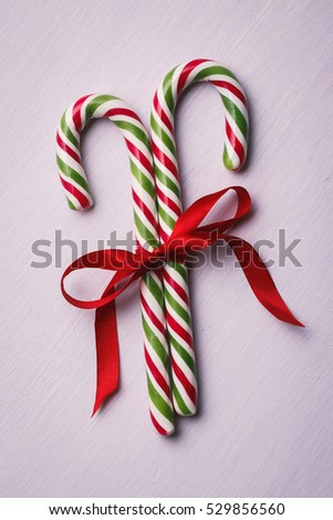Two candy tied a red ribbon on the wooden background, top view