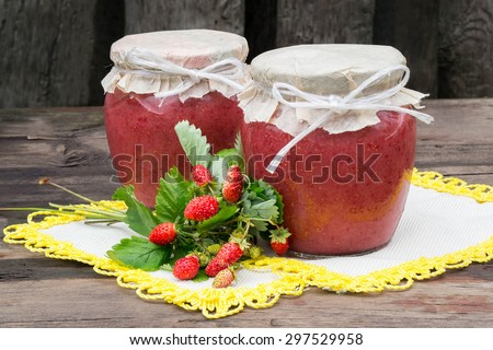 Two cans of fresh puree of wild strawberries with sugar - vitamin canned food on a napkin with yellow edging in a rustic style. Selective focus - stock photo