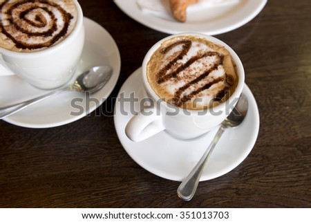 Two cappuccino cups on a table in the cafe