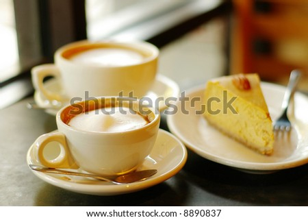 Two cappuccinos and a piece of pumpkin pie - stock photo