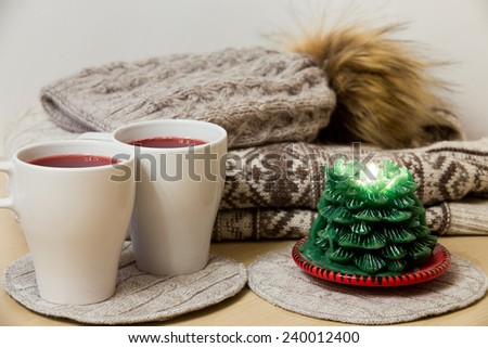 Two caps of mulled wine and a candle in front of a pile of winter clothes - stock photo