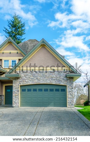 Two-car garage of a luxury house against blue sky. - stock photo