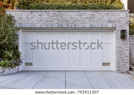 two car garage, white color, white bricks with green plants