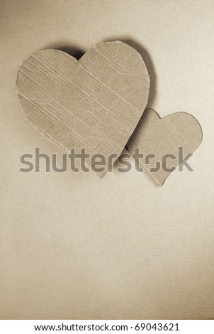 Two cardboard hearts over wrapping paper sheet