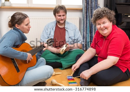 two caretaker and a mentally disabled woman makes a music therapy - stock photo