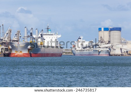 Two cargo ships unloading at a port