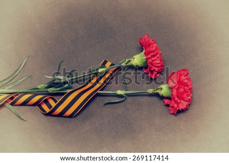 Two carnation flowers and George Ribbon. Vintage Photo. In honor of the victory in World War II - stock photo