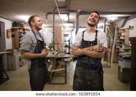 two carpenters look at the camera and smile. inside the workshop