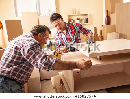 Two carpenters working at location.Repairing furniture. - stock photo