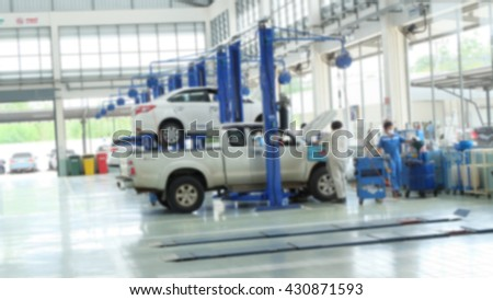 two cars on lifts and on floor in small service station. Cars prepared to diagnosis and repair.