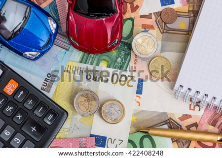 two cars with euro bills, notepad and pen