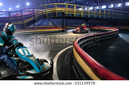 Two cart racers are racing on the grand track motion - stock photo
