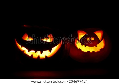 Two carved Halloween pumpkins jack-o-lantern on dark background - stock photo