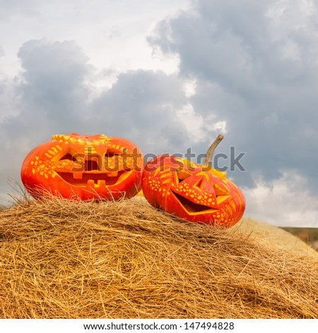 Two carved Halloween pumpkins on roll of hay outdoors - stock photo