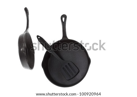 Two Cast Iron Frying Pans with spatula isolated on white - stock photo