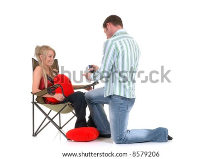 Two casual dressed young adults, teenage man and woman proposing with necklace in box. studio shot, reflective surface