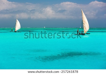 Two catamarans on amazing turquoise water in the Indian ocean next to Mnemba atoll, Zanzibar, Tanzania - stock photo