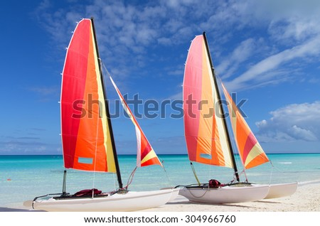 Two catamarans with its colorful sails wide open on cayo Santa Maria Cuban white sandy beach - stock photo