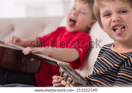 two caucasian boys playing acoustic guitar. boy sitting on couch and showing tongue - stock photo