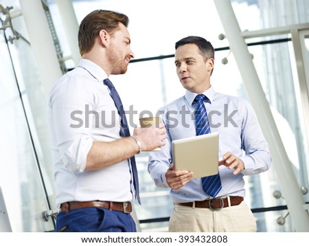 two caucasian business executives talking about business in office. - stock photo