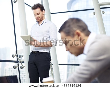 two caucasian business executives working in office using laptop and tablet computers. - stock photo
