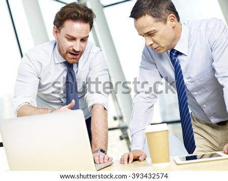 two caucasian business executives working together using laptop computer in office. - stock photo
