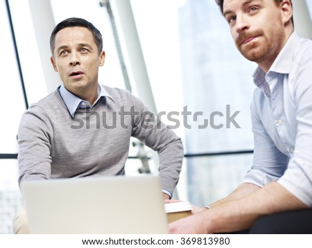 two caucasian business men looking up at projection screen while operating laptop computer. - stock photo