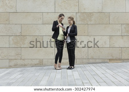 Two Caucasian Business women using a Smartphone, outside, leaning against a wall. - stock photo