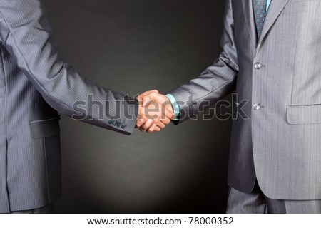 Two caucasian businessmen standing in elegant suits handshake over gray dark background. Communication, greeting, agree, congratulation meeting concept. - stock photo