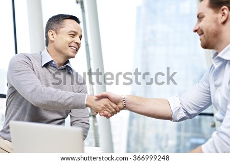 two caucasian businesspeople smiling and shaking hands in office. - stock photo