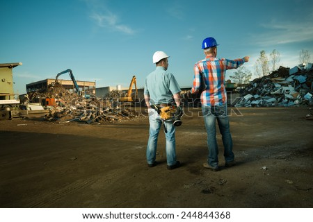 two caucasian engineers standing in recycling center outdoors, pointing at pile of scrap metal - stock photo