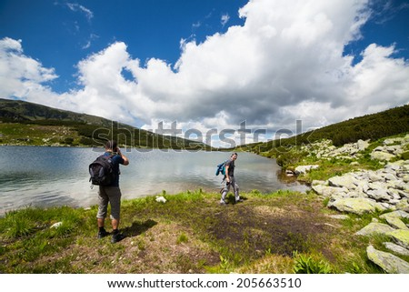 Two caucasian hikers with backpacks walking around a lake in the mountains