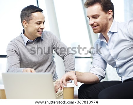 two caucasian office workers in casual wear discussing business in office. - stock photo