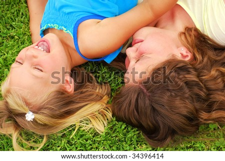 Two caucasian sisters playing and laughing in the grass - stock photo