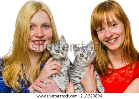Two caucasian teenage girls showing young british short hair black silver tabby spotted cats isolated on white background - stock photo