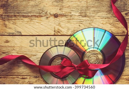 two cd disks and ribbon with bow on a wooden table - stock photo