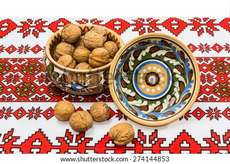 Two ceramic bowl with floral ornaments and walnuts on the tablecloth with a white background.