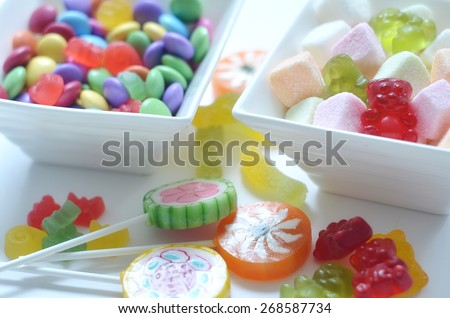 Two ceramic bowls of colored smarties, sour candies, lollipop and gummy bears on white background - stock photo