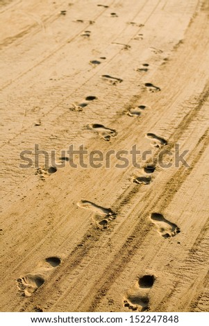 two chains of footprints in sand