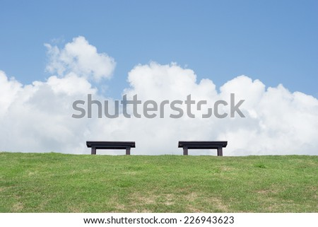 Two chair sitting empty on green grass with cloudy