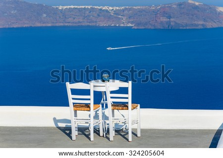 Two chairs and a small table on a beautiful terrace with a wonderful sea view in Santorini - Greece. - stock photo