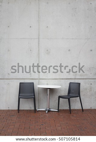 Two chairs and a table against an urban concrete wall