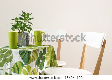 Two chairs and bright table with teacups and mint in a pot. - stock photo