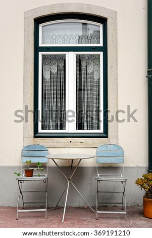 Two chairs and garden table near a window viewed from exterior