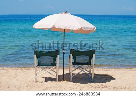 Two chairs and umbrella on the beach with sea horizon in the background - stock photo