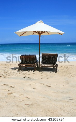 Two chairs and umbrella on the see - stock photo